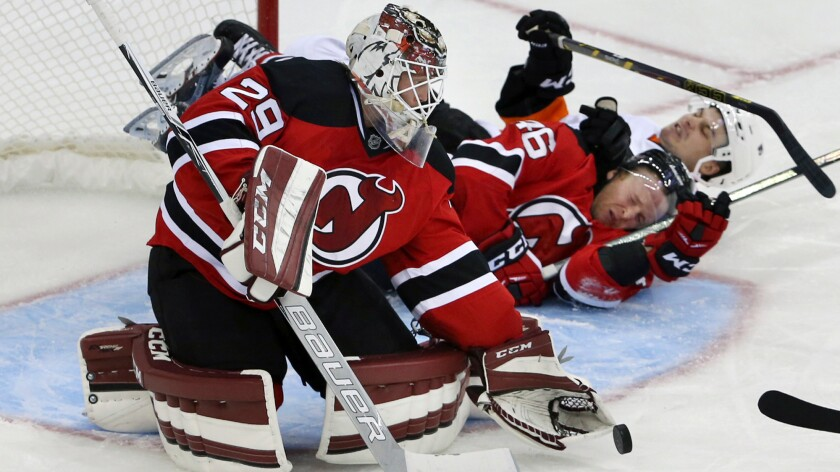 Then-New Jersey goalie Anders Lindback loses the puck as the Devils' Karl Stollery (46) and Philadelphia's Scott Laughton crash into him during an exhibition game on Sept. 26.