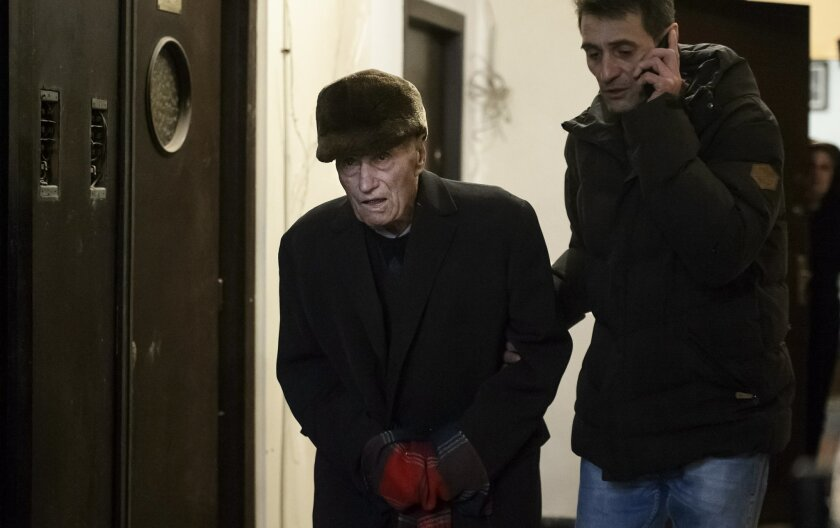 Former communist prison commander Alexandru Visinescu leaves his home escorted by a police officer dressed in civilian clothes, in Bucharest, Romania, Wednesday, Feb. 10, 2016. A Romanian appeals court has upheld a 20-year prison sentence for Visinescu, a 90-year-old communist-era prison guard conv