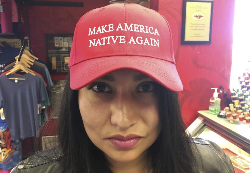 """La artista navajo Vanessa Bowen muestra su gorra con la leyenda """"que EEUU vuelva a ser nativo"""" en Albuquerque, New Mexico., 6 de julio de 2016. Bowen dice que diseñó la gorra al decidir que la consigna de Donald Trump """"que EEUU vuelva a ser grande"""" significa regresar a la época en que se discriminaba a las minorías. (AP Foto/Russell Contreras)"""