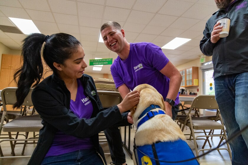 Harrah's SoCal team members bond with a pup from Canine Companions, an organization helped by the casino.