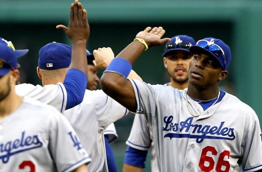 Dodgers right fielder Yasiel Puig (66) celebrates with teammates after defeating the Pittsburgh Pirates on Saturday.