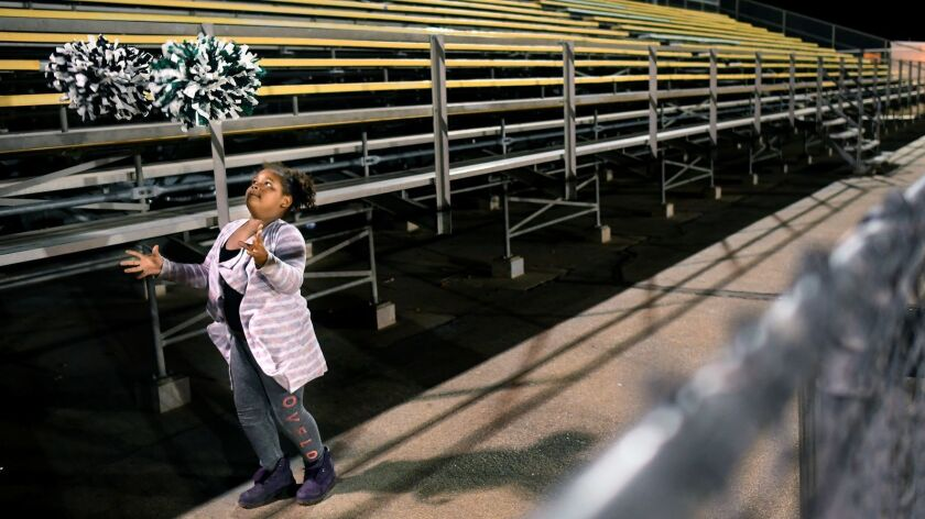 Sanai Mayfield plays with pom-poms on the Hawkins High side of the bleachers during a football playoff game at San Fernando in 2017.