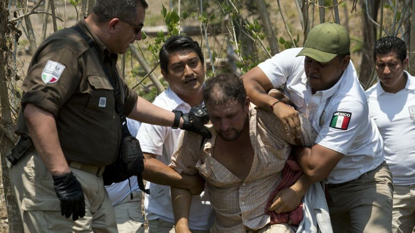 A Central American migrant is detained by Mexican immigration agents on the highway to Pijijiapan, M