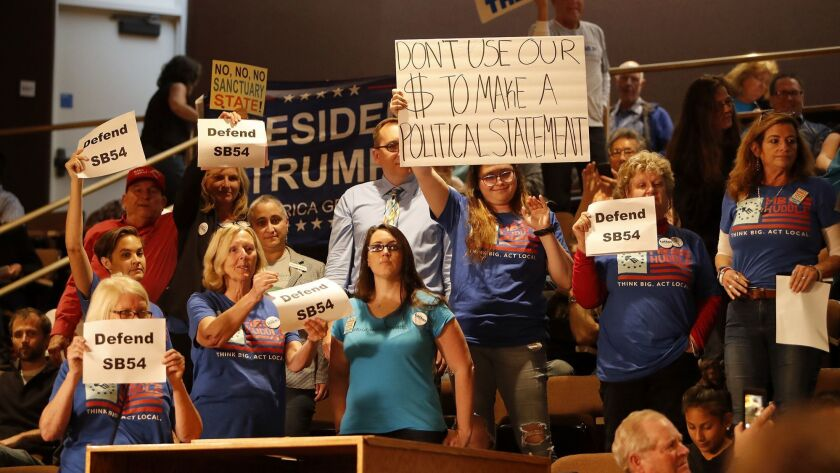 Supporters of Senate Bill 54, or the California Sanctuary State Bill, hold up signs during a Hunting