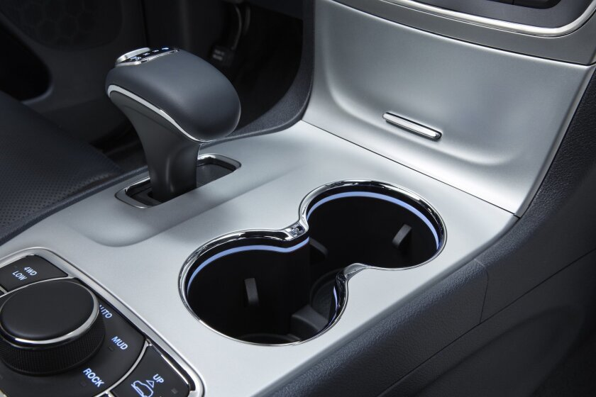 This photo provided by Fiat Chrysler Automobiles shows the interior of a 2014 Jeep Grand Cherokee Overland. U.S. auto safety investigators have determined that electronic gear shifters, like the one at upper left, in some newer Fiat Chrysler SUVs and cars are so confusing that drivers have exited t