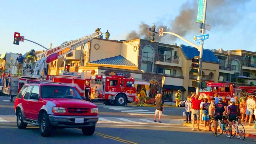 Spectators gather at the corner of Pearl Street and Draper Avenue in La Jolla to watch firefighters extinguish the accidental fire at Sammy's Woodfired Pizza within 30 minutes on Sept. 5, 2015.