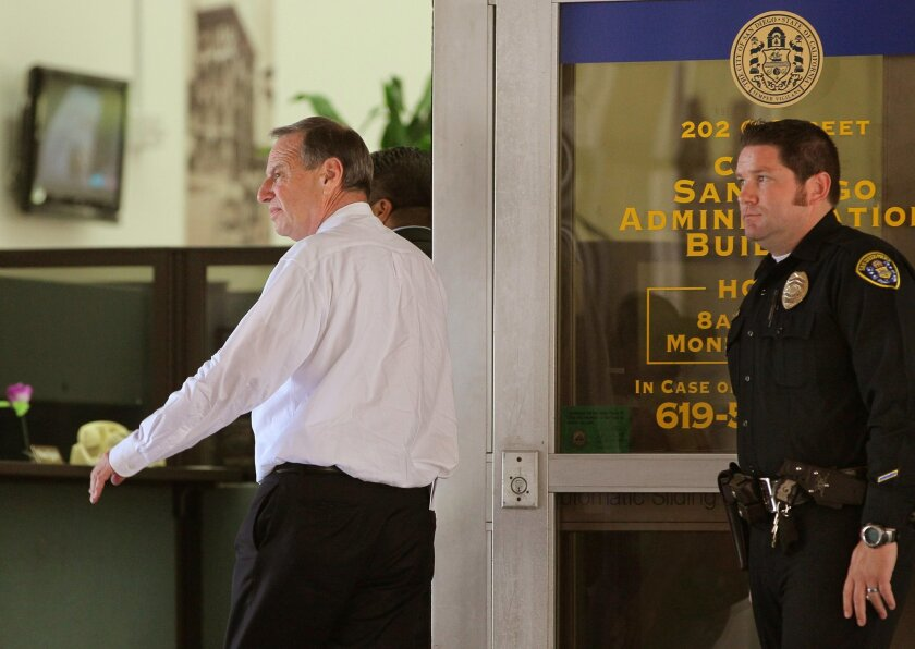 San Diego Mayor Bob Filner enters City Hall though its main entrance at 2:14 p.m. as a San Diego Police Officer stands by.