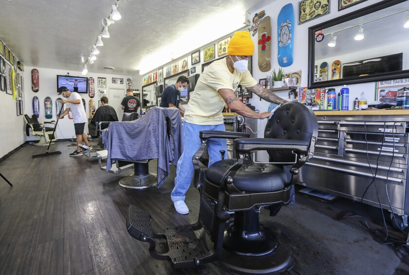 Maintaining hygiene rules, Leucadia Barber Shop manger Emiliano Zermeno (right) wipes down his barber chair