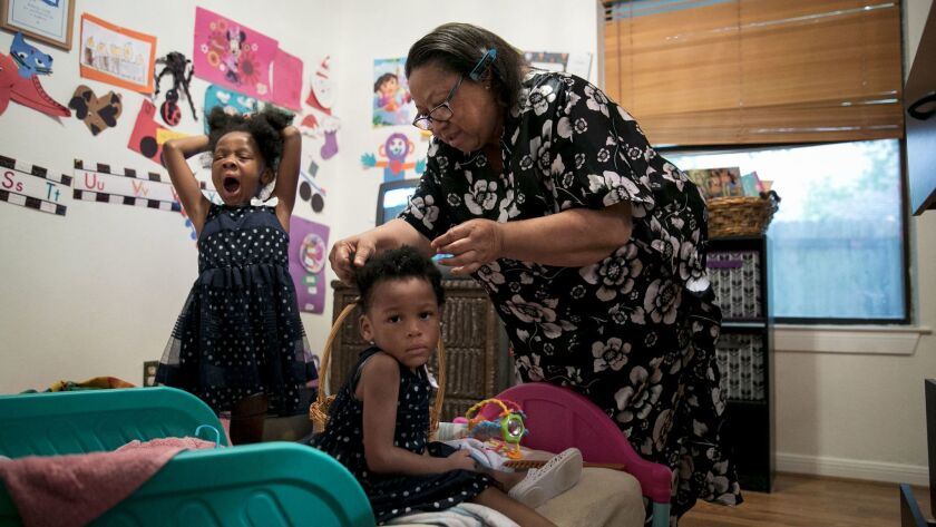 Pflugerville, Texas - July 2, 2017: Ms. Givens-Perkins brushes her granddaughters' hair for church.
