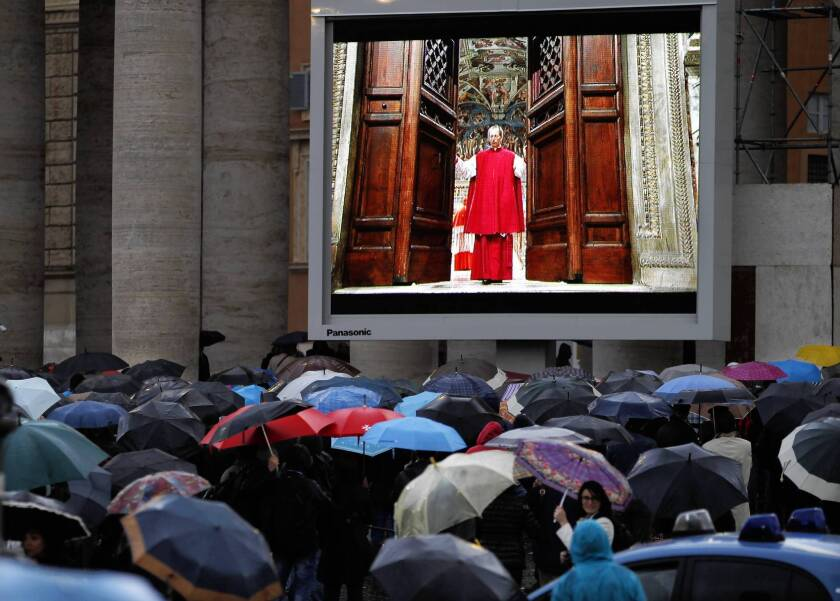 People watch a video monitor in St. Peter's Square in Vatican City as the doors to the Sistine Chapel are closed at the start of the conclave to elect the next pope. The cardinals' first vote produced no winner.