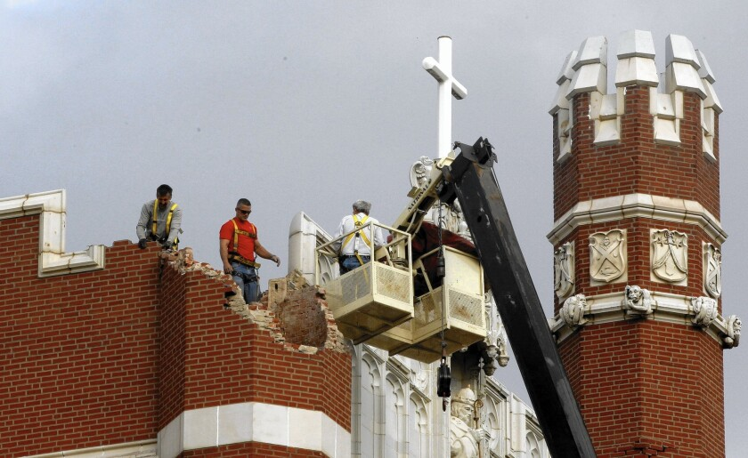 Maintenance workers inspect the damage to one of the spires on Benedictine Hall at St. Gregory's University after a magnitude-5 earthquake in Shawnee, Okla., in 2011.