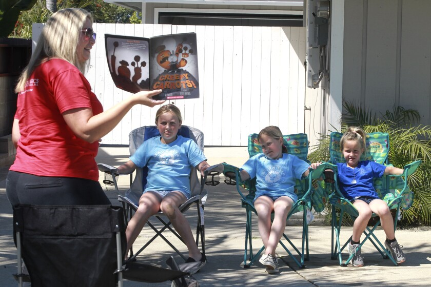 "Library Media Technician for Calavara Hills Elementary School Lindsay Rudy reads ""Creepy Carrots!"" to Hailey Rutledge, 10, left, and her sisters Mia, 8, center, and Kate, 6, while in front of the Rutledge family's home on Friday March 27, 2020 in Carlsbad, California."