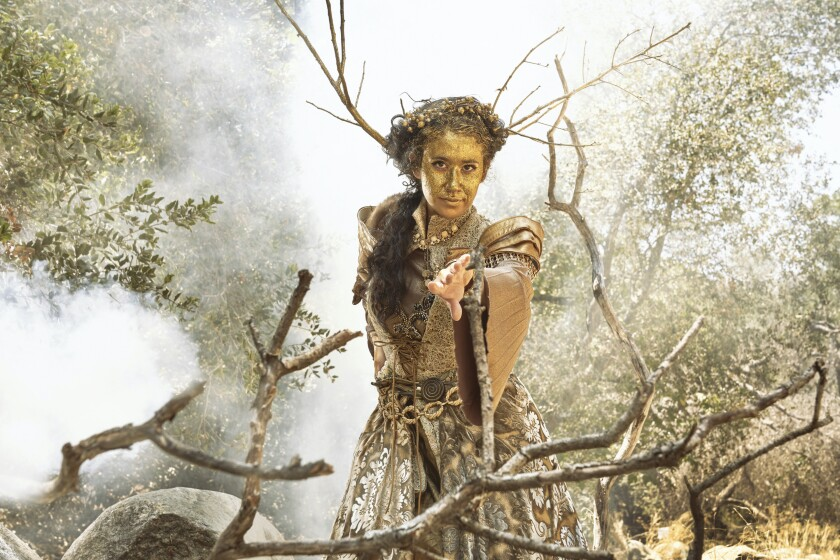 A person in a costume stands among bare tree branches.