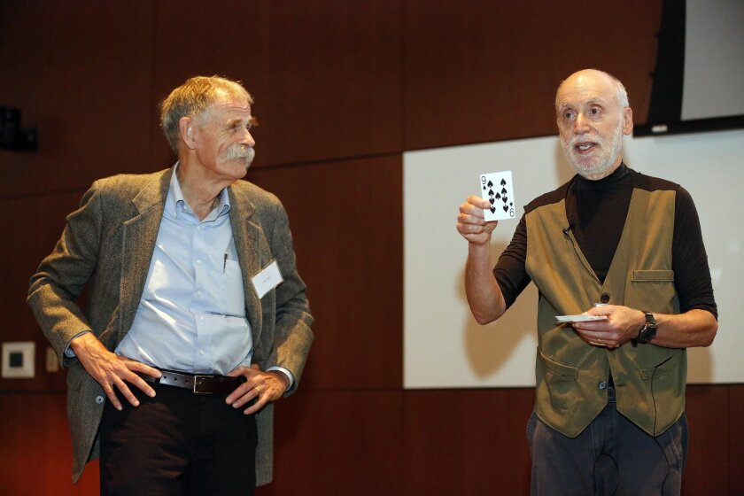 """Richard Horn, demonstrates a magic trick to attendees of a brain research educational event for the public, about the state of research and how it is helping patients. Horn's presentation was entitled """"The Brain, the Mind, and Magic: Making a Fool of Parkinson's"""". He is accompanied by UCSD research"""