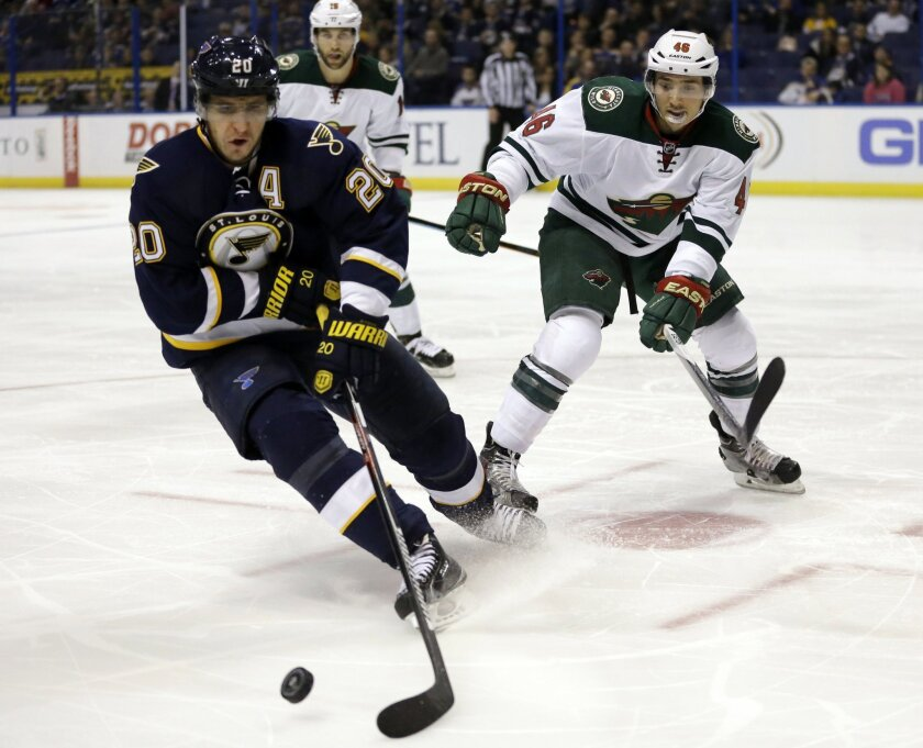 St. Louis Blues' Alexander Steen, left, controls the puck as Minnesota Wild's Jared Spurgeon, right, watches during the second period of an NHL hockey game Saturday, Oct. 31, 2015, in St. Louis. (AP Photo/Jeff Roberson)