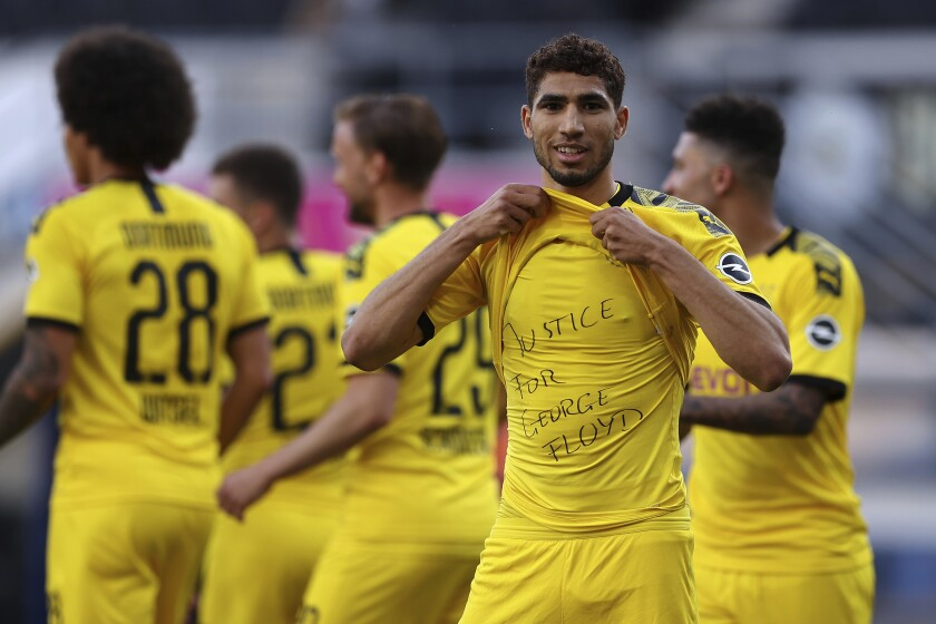 FILE - In this Sunday, May 31, 2020 file photo Achraf Hakimi Mouh of Borussia Dortmund celebrates scoring his teams fourth goal of the game with 'Justice for George Floyd' written on his under shirt during the German Bundesliga soccer match between SC Paderborn 07 and Borussia Dortmund at Benteler Arena in Paderborn, Germany. Since George Floyd's death in the U.S. state of Minnesota last week, his face has been painted on walls from Nairobi, Kenya to Idlib, Syria. Floyd's name has been inked on the shirts of soccer players and chanted by crowds from London and Cape Town to Tel Aviv and Sydney. (Lars Baron/Pool via AP, File)