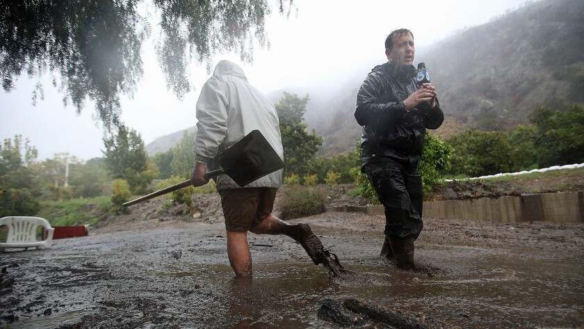 An Azusa man trying to keep drains clear trudges through flowing mud past KTLA reporter Chris Burrous in February 2014.
