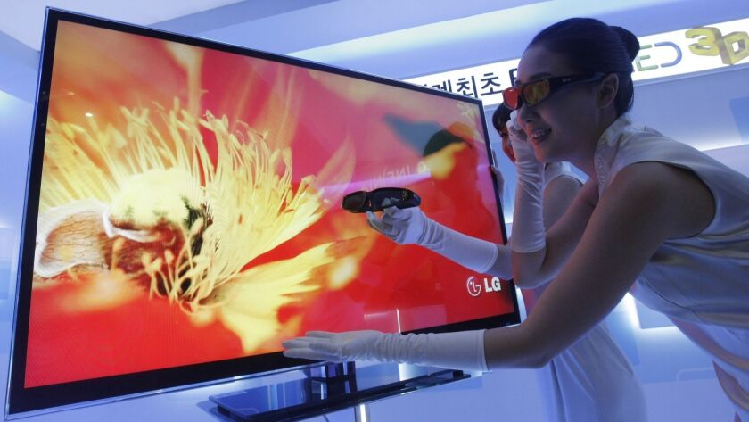 "A model helps unveil LG Electronics' LED 3D television in Seoul in March 2010. The electronics company will release a 65-inch ""rollable-screen"" television next year."