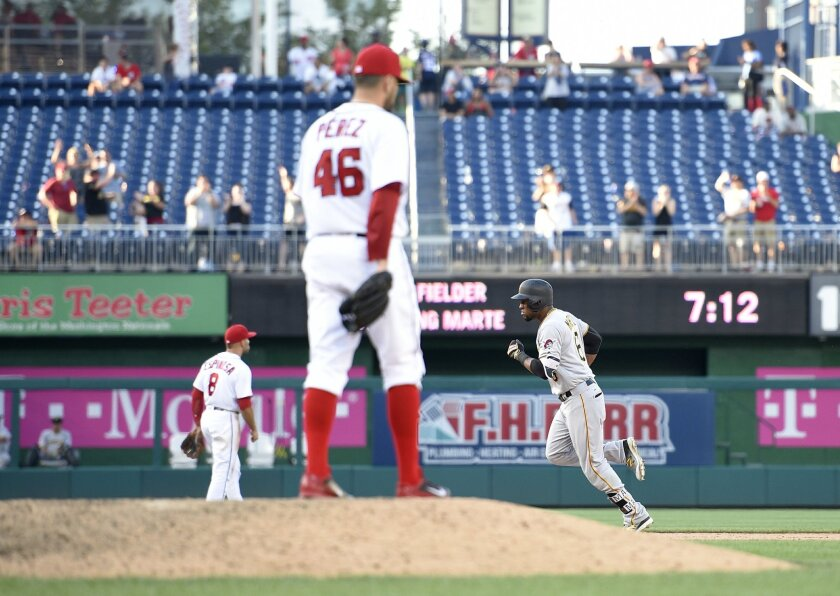Pittsburgh Pirates' Starling Marte, right, rounds the bases after he hit a home run as Washington Nationals relief pitcher Oliver Perez (46) looks on during the 18th inning of a baseball game, Sunday, July 17, 2016, in Washington. The Pirates won 2-1 in 18 innings. (AP Photo/Nick Wass)