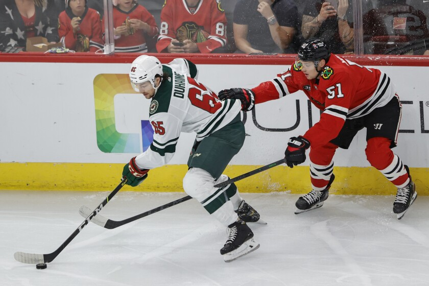Minnesota Wild right wing Brandon Duhaime (65) keeps the puck away from Chicago Blackhawks defenseman Ian Mitchell (51) during the first period of an NHL preseason hockey game, Saturday, Oct. 9, 2021, in Chicago. (AP Photo/Kamil Krzaczynski)