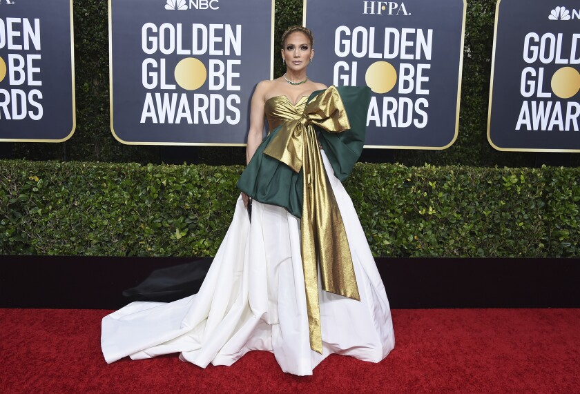 Jennifer Lopez stands on a red carpet in a formal green and white gown with voluminous skirt and oversized gold bow.