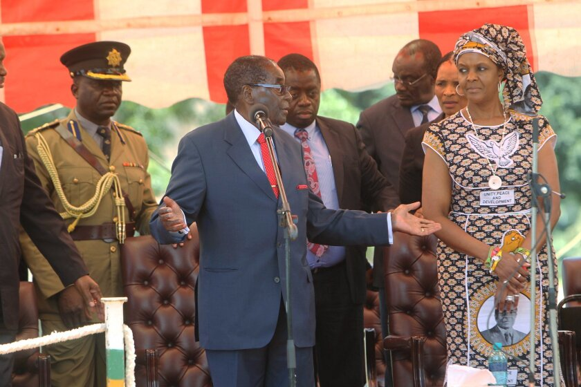 In this image taken on  Wednesday Feb, 10, 2016  Zimbabwean President Robert Mugabe  addresses supporters at the party headquarters in Harare, while his wife Grace looks on.  Mugabe, the world's oldest head of state, recently warned officials of his ZANU-PF party to stop insulting each other. A lot