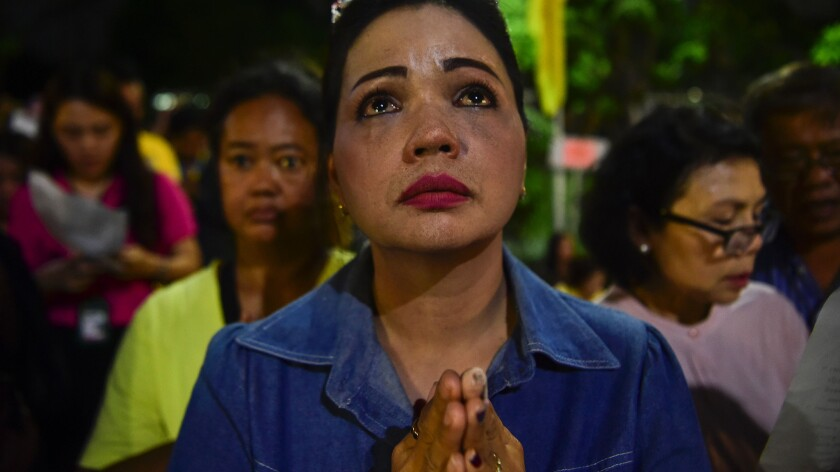 A Thai woman prays outside the hospital where King Bhumibol Adulyadej was being treated.