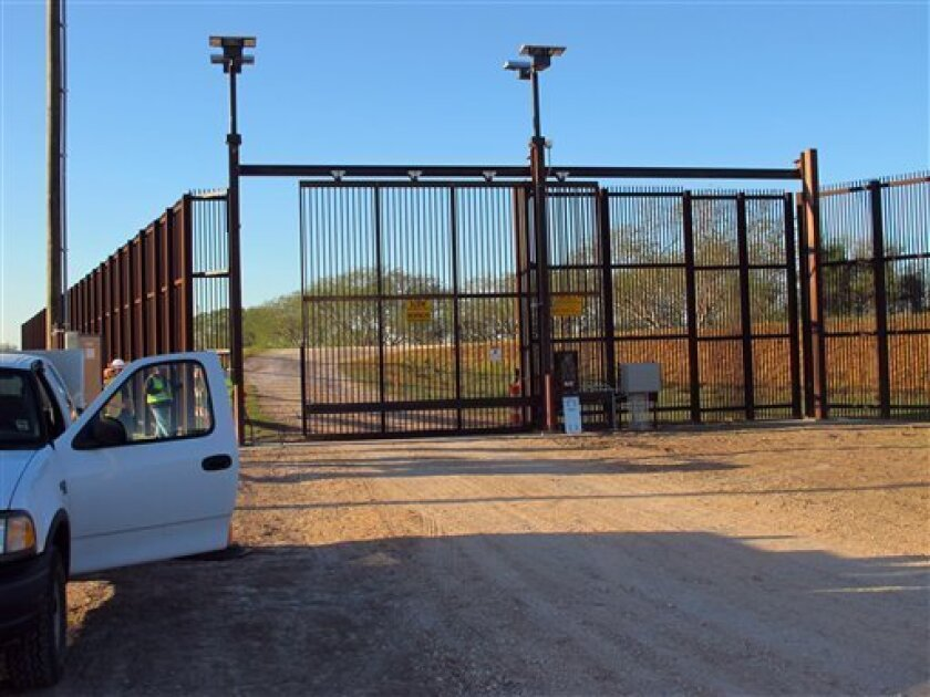 In this Jan. 27, 2012 photo, government contractors test a new gate in the border fence in Brownsville, Texas. A year after completion of the border fence the government is installing 44 gates in South Texas. (AP Photo/Chris Sherman)