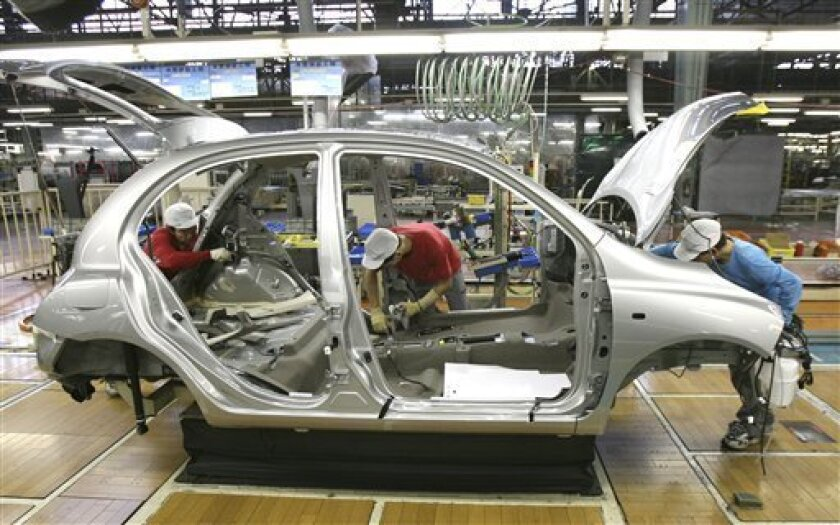 Nissan Motor Co. assembly line employees work on the Nissan March at a plant in Yokosuka, southwest of Tokyo, in this photo taken on Nov. 29, 2006. Nissan will shift some production of its top-selling compact car as the March and its counterpart model for French alliance partner Renault SA, now pro