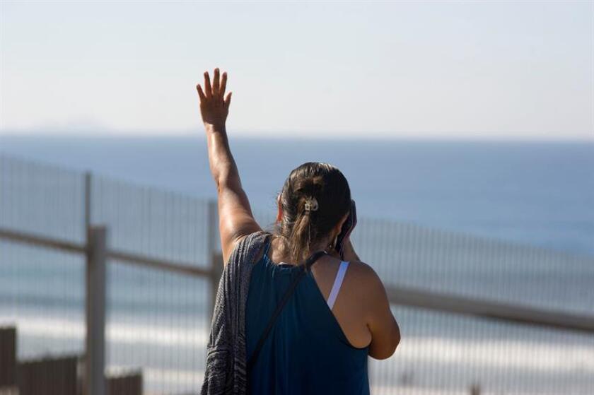 Cruz Gutiérrez saluda a su hijo desde el otro lado de la fronters, en el Parque de la Amistad, en San Diego (Estados Unidos) hoy, domingo 18 de noviembre de 2018. EFE