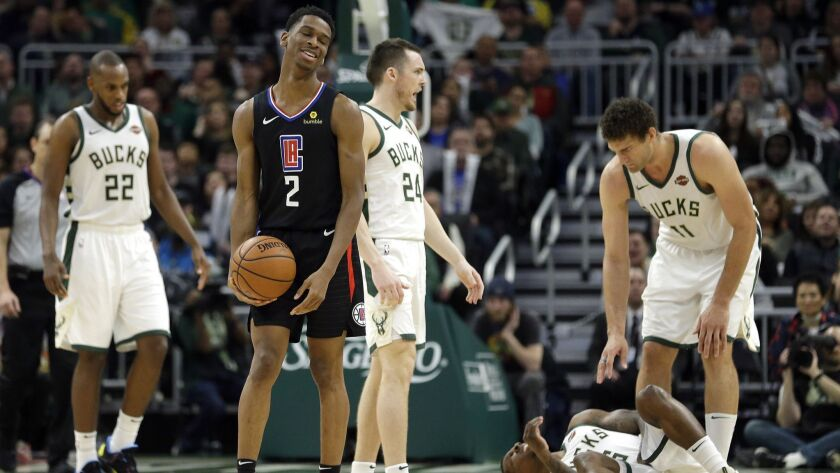 LA Clippers' Shai Gilgeous-Alexander (2) reacts after fouling Milwaukee Bucks' Eric Bledsoe, bottom