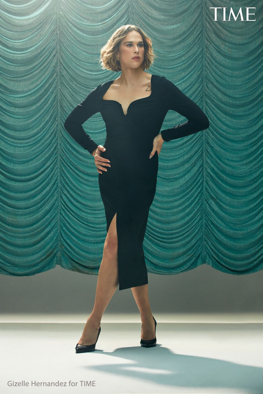 A woman poses in a black cocktail dress