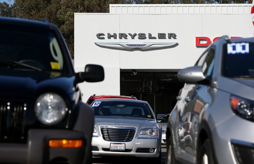 Cars are displayed on the sales lot of a Chrysler dealership on January 3, 2013 in Colma, California. Analytics giant IHS Inc. said it has signed an agreement to acquire R.L. Polk & Co. for $1.4 billion.
