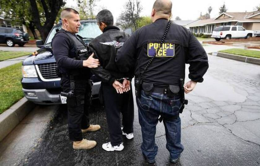 David A. Martin of ICE, left, talks to a detainee during an arrest in Chatsworth. The Trust Act would prohibit local authorities from complying with federal detention requests except when a suspect has been charged with a serious or violent crime.