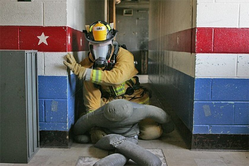 Recruit Brian Luke, 26, with his masked blacked out, searched for a dummy as part of a rescue exercise. Trainees (below), staying as low as possible, felt a door to check for heat before entering a room. (David Brooks / Union-Tribune)