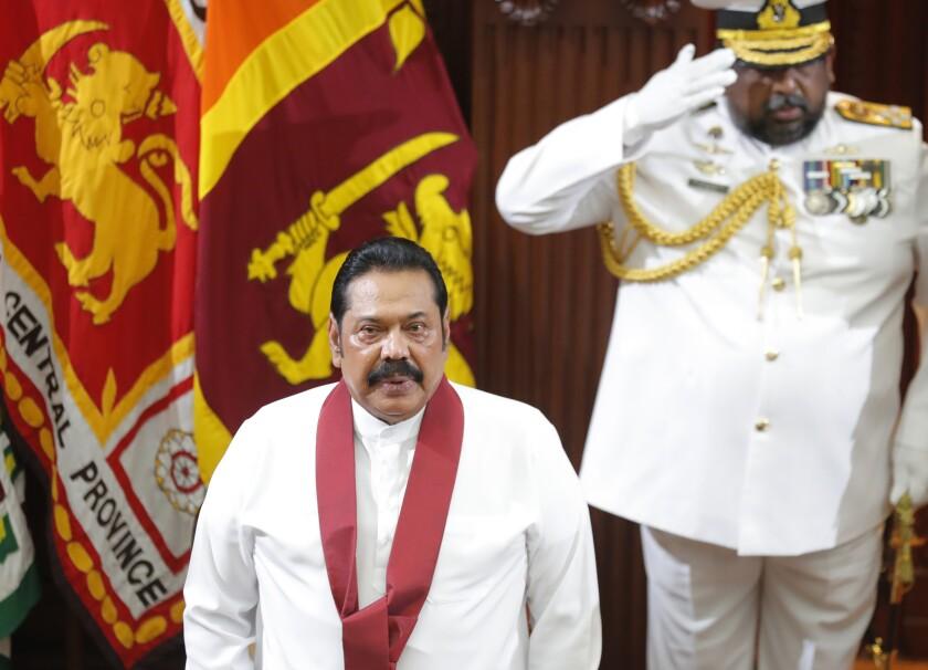Sri Lanka's new Prime Minister Mahinda Rajapaksa stands for the national anthem at the presidential secretariat in Colombo, Sri Lanka, Thursday, Nov. 21, 2019. President Gotabaya Rajapaksa is expected to name his Cabinet later, on the advice of the new prime minister. (AP Photo/Eranga Jayawardena)