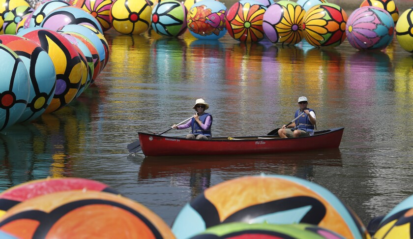 "The public art project ""Spheres at MacArthur Park"" is covering the park's lake in a sea of colorful balls. Two volunteers paddle their way through the installation on Saturday morning."