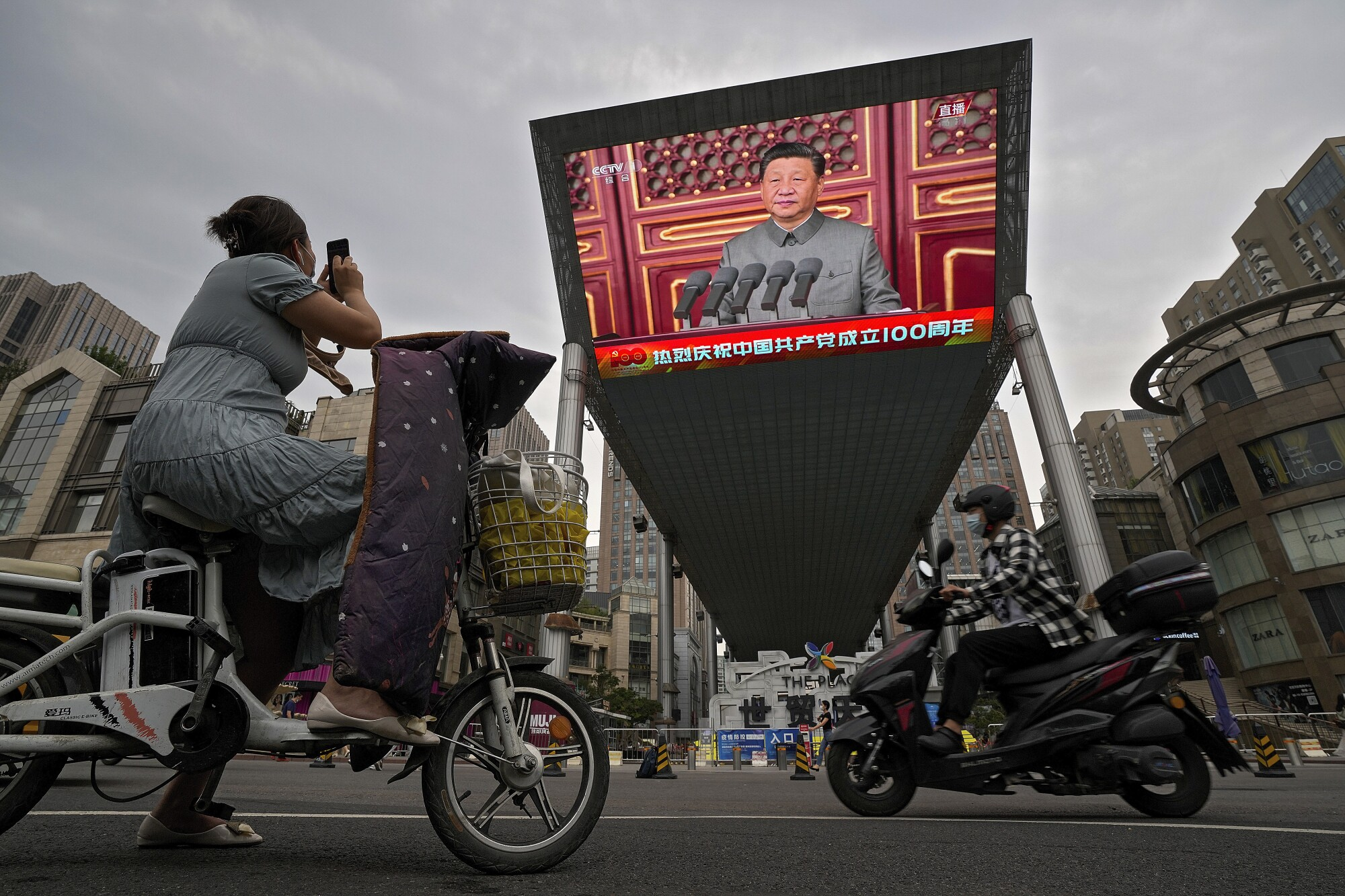 A woman on her electric-powered scooter films a large video screen showing Chinese President Xi Jinping.