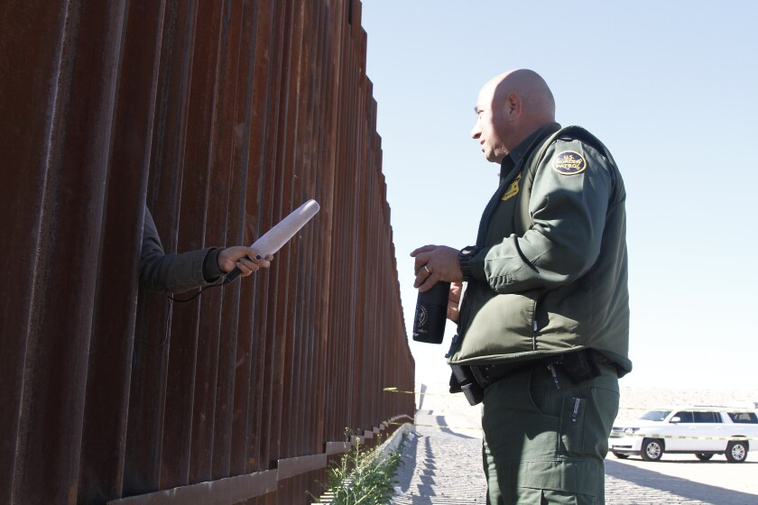 A journalist in Anapara, Mexico, sticks her microphone through a through a border fence to interview a Border Patrol agent following a training exercise on Friday, Jan. 31, 2020, in Sunland Park, New Mexico. Journalists in Mexico filmed the use-of-force exercises through gaps in the bollard-style wall. (AP Photo/Cedar Attanasio)