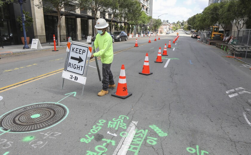A work crew begins construction at Market and 14th Streets of a new promenade/ double sidewalk area.