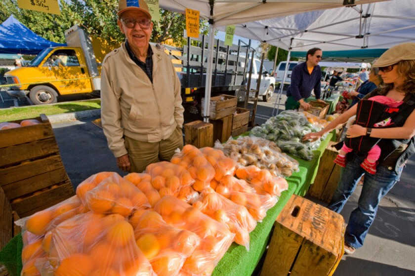 Robert Knight Sr. and his son sold produce, including Washington navel oranges, Hayward kiwifruit, and Bacon avocados, at the Palm Springs farmers market.