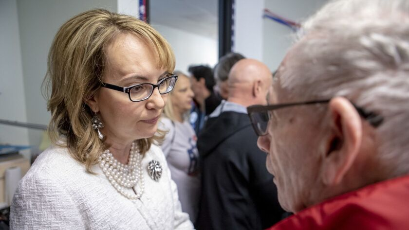 Former Rep. Gabrielle Giffords talks with Leonard Brown, 90, who came to hear her speak at a rally at congressional candidate Mike Levin's Solana Beach campaign office on Sunday.
