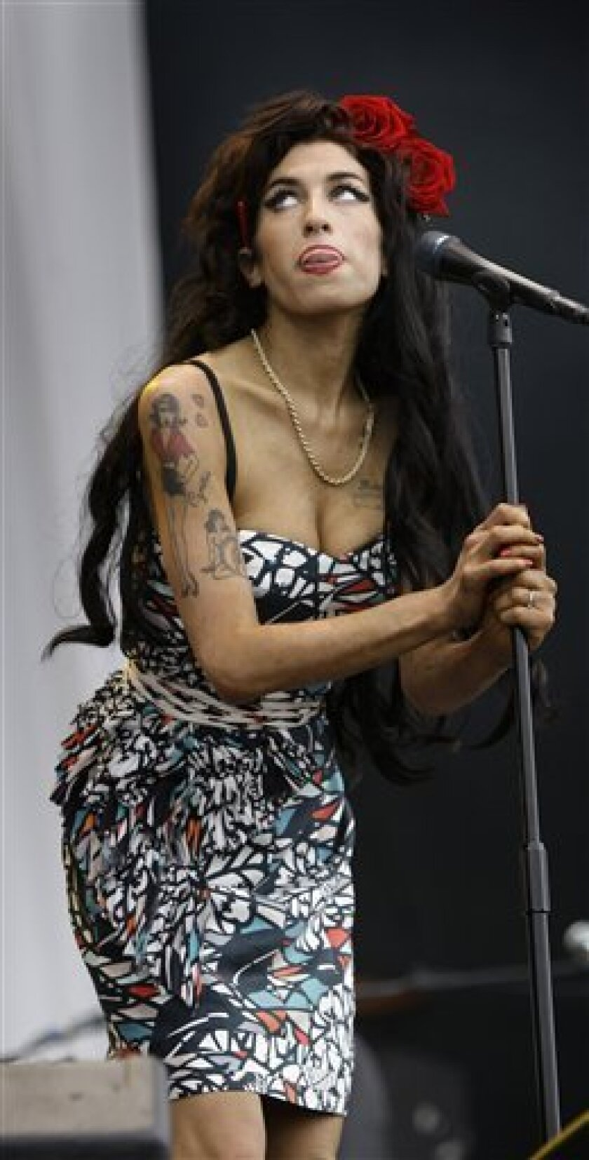 FILE - In this Sunday, Aug. 17, 2008, file photo, British singer, Amy Winehouse performs at the V Festival, near Chelmsford, England. A British newspaper says singer Amy Winehouse has won a court order banning the paparazzi from pursuing her outside her London home. The Guardian reports that she sought the order to ban photographers if they follow her or approach her within 100 meters (yards) of her home. (AP Photo/Joel Ryan, File)