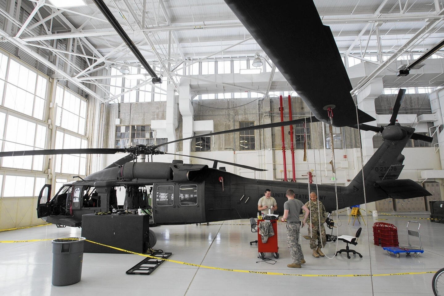 Sgt. Daniel Davis, left, Specialist Mark Enriquez, and Sgt. Sink Nuom, right, work on a UH-60 Black Hawk at the Los Alamitos Joint Forces Training Base on Monday.