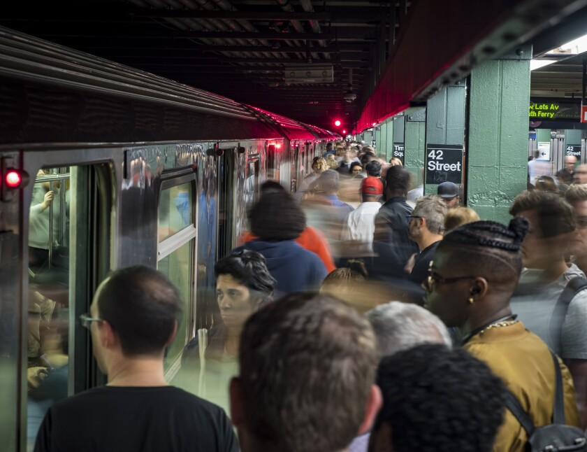 Straphangers makes their way into crowded train at the 42nd Street subway station.