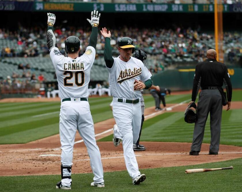 Stephen Piscotty (c) y Mark Canha (i) de Athletics celebran durante su juego de la MLB. EFE/Archivo