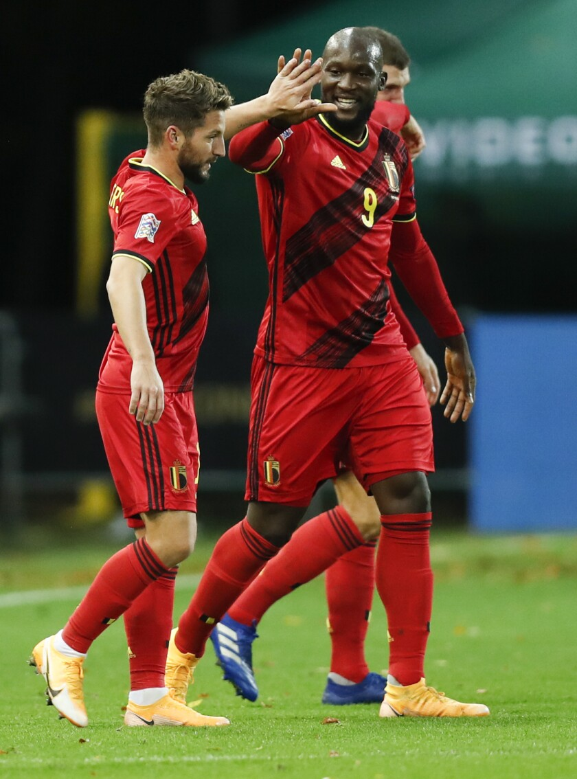 Belgium's Dries Mertens, left, celebrates with teammate Romelu Lukaku after scoring his team's second goal during the UEFA Nations League soccer match between Belgium and England at the King Power stadium in Leuven, Belgium, Sunday, Nov. 15, 2020. (AP Photo/Francisco Seco)
