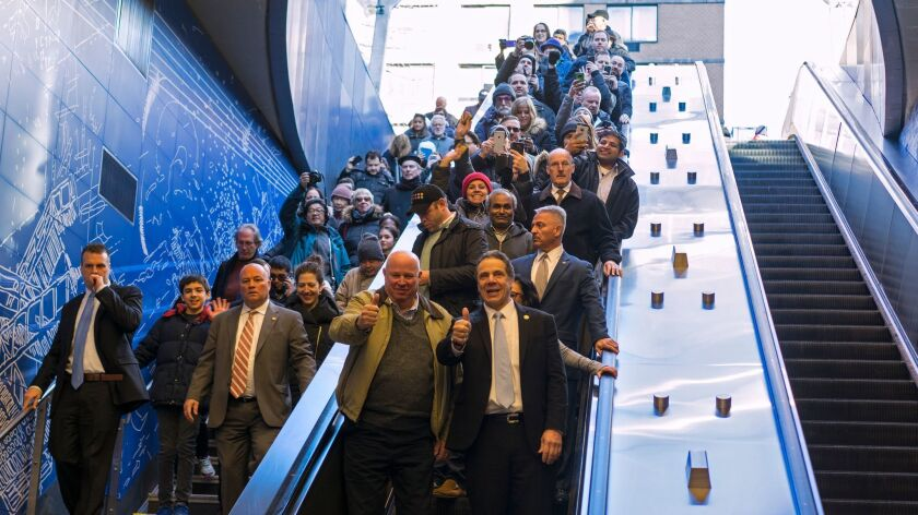 Metropolitan Transportation Authority Chairman and Chief Executive Thomas Prendergast, center left, and New York Gov. Andrew Cuomo, center right, enter the newly opened 96th Street station of the Second Avenue subway along with other riders.