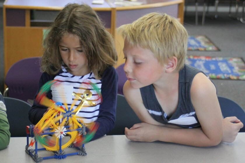 Lilyah Baroudi and Landon Thompson study how gears work.