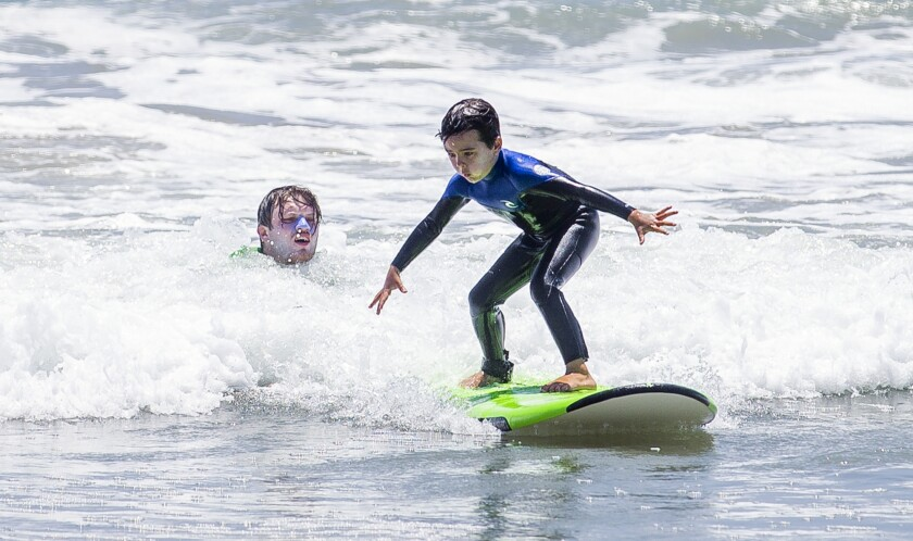 Declan Morrison, 6, from Claremont, rides a wave during a surf camp at Huntington Dog Beach on Tuesday.